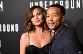 """FILE - John Legend, executive producer of """"Underground,"""" poses with his wife Chrissy Teigen at the season two premiere of the television series."""