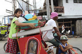 Residents with their belongings ride on a tricycle cab to an evacuation center in Tacloban city, central Philippines, Dec. 4,  2014.