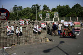 Egyptians walk between brick barricades erected along a street that leads to Rabaah al-Adawiya mosque, where supporters of Egypt's ousted President Mohammed Morsi have installed a camp and hold daily rallies at Nasr City, in Cairo, July 29, 2013.