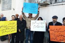 In this image sent to and verified by VOA Persian, Iranian teachers stage a protest in the northeastern city of Mashhad, Feb, 14, 2019. The yellow sign calls for teachers to be paid at equal rates to other public sector workers, while the blue sign s