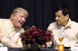 U.S. President Donald Trump speaks with Philippines President Rodrigo Duterte during the dinner marking ASEAN's 50th anniversary in Manila, Philippines, Nov. 12, 2017.