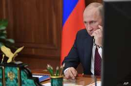 FILE - Russian President Vladimir Putin speaks on the phone at the Kremlin, in Moscow, Russia, Nov. 15, 2017.