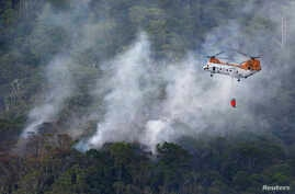 A U.S. military helicopter fights the fire following a crash by another U.S. military CH-46 helicopter, inside Camp Hansen in central Okinawa, on Japan's southern island, in this photo taken by Kyodo, Japan, August 5, 2013.