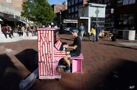 Street Pianos: In this Sunday, Sept. 25, 2016 photo Scott Frazer, of Medford, Mass., plays a piano on the sidewalk in the Harvard Square neighborhood of Cambridge, Mass. A number of working pianos painted by local artists have been placed around Bost