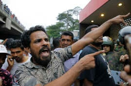 A supporter of newly appointed Sri Lankan prime minister Mahinda Rajapaksa shouts at police officers outside the Petroleum Ministry building  in Colombo, Sri Lanka, Oct. 28, 2018.