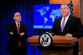 Elliott Abrams, left, listens to Secretary of State Mike Pompeo talk about Venezuela at the State Department in Washington, Jan. 25, 2019.