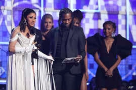 "Cardi B, left, accepts the award for best rap album for ""Invasion of Privacy"" at the 61st annual Grammy Awards, Feb. 10, 2019, in Los Angeles, California."