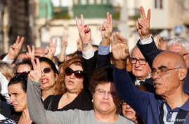 People sing the Maltese national anthem as they show a peace sign while attending a funeral ceremony of journalist Daphne Caruana Galizia, who was murdered in a car bomb attack, at the Rotunda Parish Church in Mosta, Malta, Nov. 3, 2017.