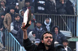 An Afghan demonstrator holds a copy of a half-burnt Quran,