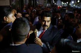 Venezuela's President Nicolas Maduro (C) greets supporters after his meeting with representatives of the Venezuelan coalition of opposition parties Mesa de la Unidad (MUD) and the Union of South American Nations' foreign ministers in Caracas, April 8...