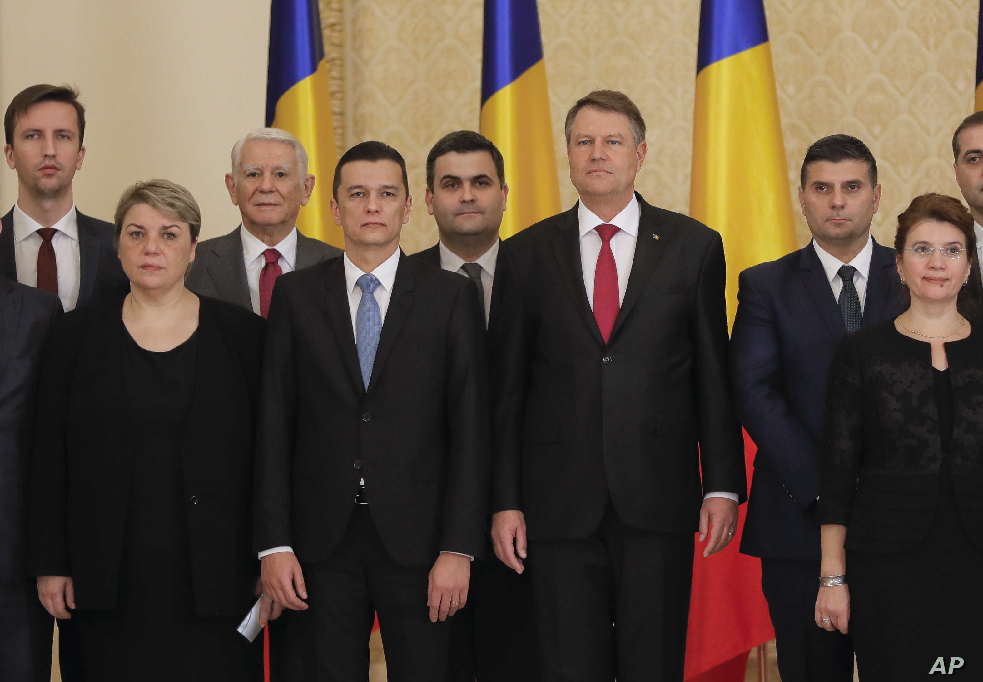 Romanian Prime Minister Sorin Grindeanu, center left, poses for the media next to Romanian President Klaus Iohannis after the swearing in ceremony for his cabinet, in Bucharest, Romania, Jan. 4, 2017.