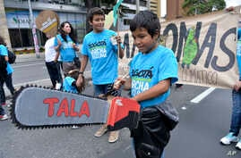 FILE - A boy wields a toy chainsaw to call attention to the role of deforestation in climate change, during the People's Climate March in Bogota, Sept. 20, 2014.