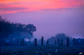 Displaced people who fled the recent fighting between government and rebel forces in Bor by boat across the White Nile, prepare to sleep in the open at night in the town of Awerial, South Sudan, Jan. 1, 2014.
