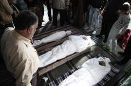 Syrians and Jordanians look at the bodies of, Emara al-Zoabi, 7 months, left, Moath al-Rawashdy, 30 years, right, and Ahmed al Natoor, 62 years, center, who were killed from Syrian government forces shelling in Ramtha City, north Amman, Jordan, Decem