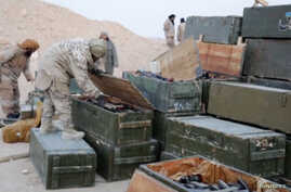 Islamic State fighters search weapon boxes in a Russian base in what is said to be Palmyra, Syria, in this still image taken from video uploaded to social media on Dec. 13, 2016.