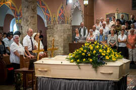 Marcelline Udry (3rd-L), one of the daugther of late Marcelin and Francine Dumoulin, the couple found on a receding glacier in the Swiss Alps 75 years after they had disappeared, attends her parents' funeral ceremony in front of their coffins on July