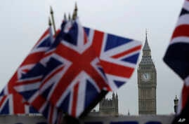 Union flags displayed on a tourist stall, backdropped by the Houses of Parliament and Elizabeth Tower containing the bell know as Big Ben, in London, Feb. 8, 2017.