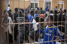 Would-be immigrants react from behind the fence of a temporary immigrant holding center after crossing the border from Morocco to Spain's north African enclave of Melilla March 18, 2014.