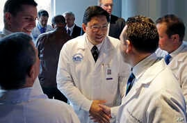 Dr. Dicken Ko, director of Massachusetts General Hospital's urology program, shakes hands with surgical team members after a news conference at the hospital in Boston to announce the first penis transplant in the United States, May 16, 2016.