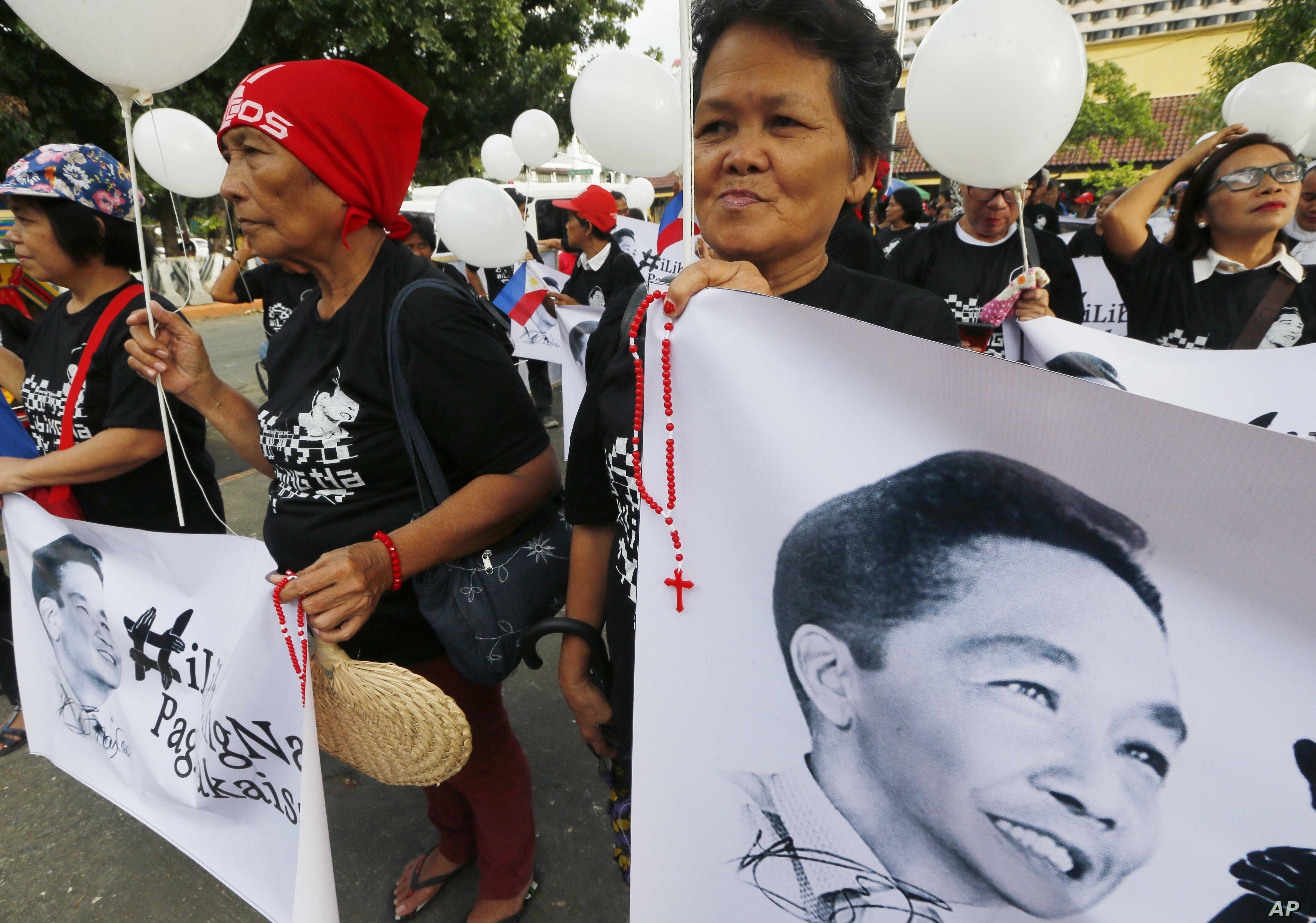 Supporters of the late Philippine dictator Ferdinand Marcos display his images prior to marching towards the Supreme Court for an overnight vigil, Nov. 7, 2016.