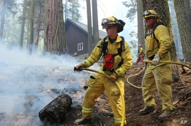 In this photo provided by the U.S. Forest Service, firefighters hose down a hotspot near a ranger station as they fight the Rim Fire in Yosemite National Park in California, Sept. 1, 2013.