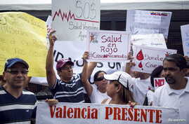 Protesters in front of a social security office hold placards demanding medicines in Caracas, Venezuela, Aug. 27, 2015.