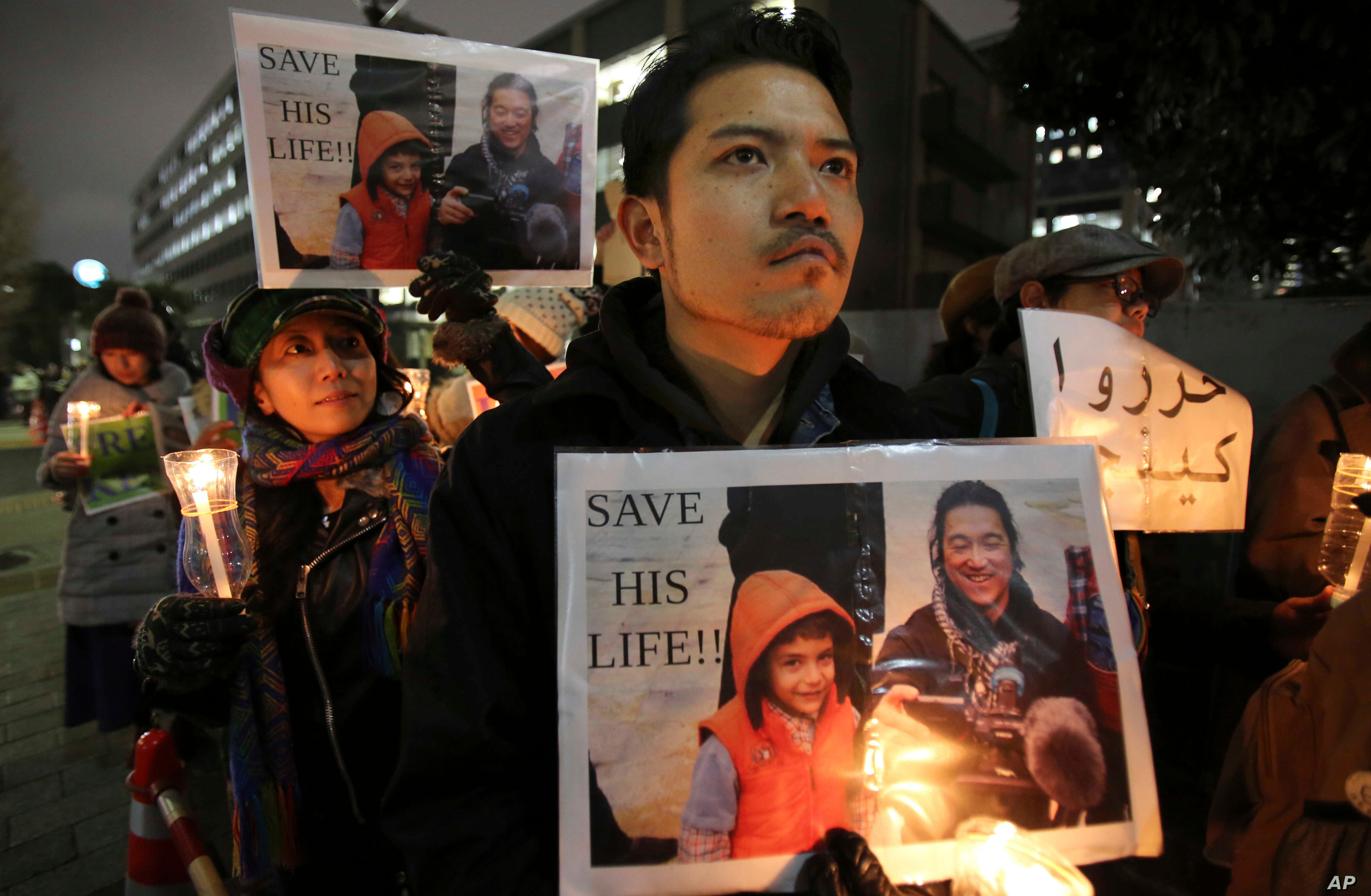 FILE - Protesters holding signs bearing a photo of Japanese journalist Kenji Goto, who was taken hostage by the Islamic State group, appeal to the government to save Goto during a rally in front of the prime minister's official residence in Tokyo.