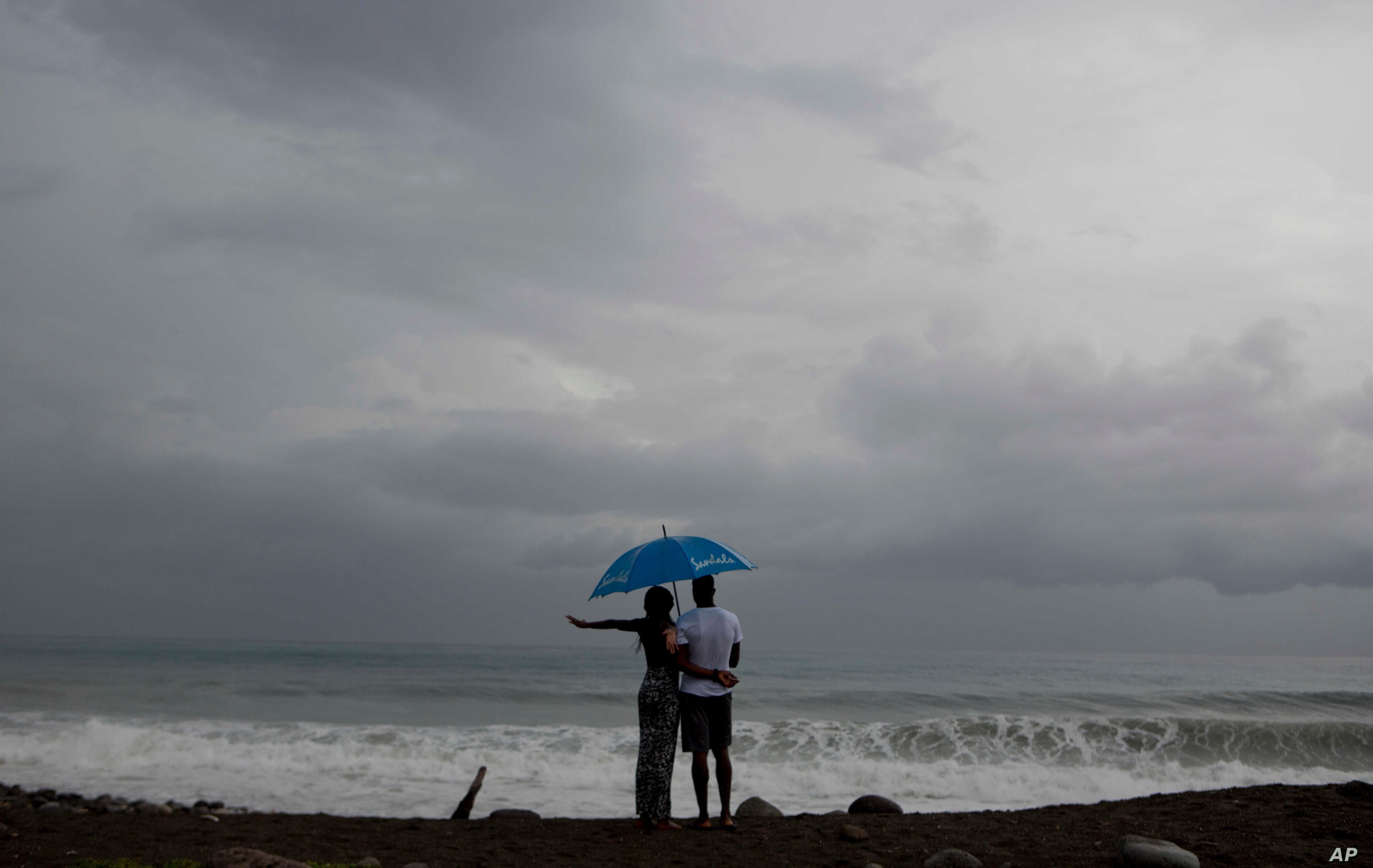 A couple watches the sea under rain in Kingston, Jamaica, Oct. 2, 2016. A depression in the southwestern Caribbean region is expected to become a tropical storm later in the day or overnight, the U.S. National Hurricane Center says.