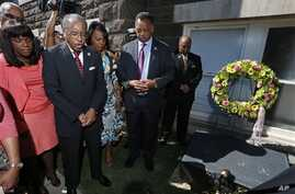 Rev. Julius Scruggs, second from left, leads people in prayer during a wreath laying ceremony at the 16th Street Baptist Church in Birmingham, Ala., Sunday, Sept. 15, 2013. The congregation gathered outside the church for the wreath laying ceremony a