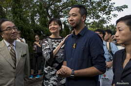 Civic Party member and lawyer Audrey Eu pats activist and Civic Party member Ken Tsang Kin-chiu as Tsang arrives at the Central Police Station to be arrested on the charges of obstructing and assaulting police officers during the Occupy movement a ye