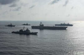 The Ronald Reagan Strike Group ship's the aircraft carrier USS Ronald Reagan, the guided-missile cruiser USS Antietam and the guided-missile destroyer USS Milius conduct a photo exercise with the Japan Maritime Self-Defense Force ship's the helicopte