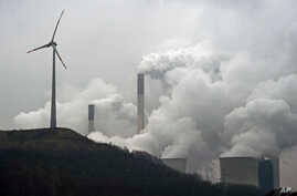 FILE - In this file photo dated Monday, Dec. 1, 2014, a wind turbine overlooks the coal-fired power station in Gelsenkirchen, Germany.
