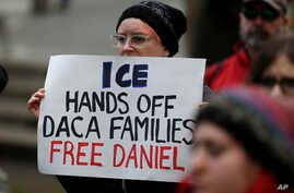 """A protester holds a sign that reads """"ICE Hands Off DACA Families Free Daniel,"""" during a demonstration in front of the federal courthouse in Seattle, Feb. 17, 2017."""