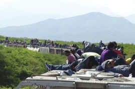 FILE - People hoping to reach the U.S. ride atop the wagon of a freight train, known as La Bestia (The Beast) in Ixtepec, in the Mexican state of Oaxaca, June 18, 2014.