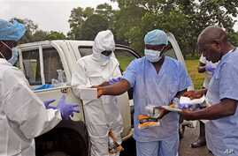 Health workers are handed personal protective gear by a team leader, right, before collecting the bodies of the deceased from streets in Monrovia, Liberia, Saturday, Aug. 16, 2014. New figures released by the World Health Organization showed that Lib