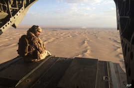 FILE - An Emirati gunner watches for enemy fire from the rear gate of a United Arab Emirates Chinook military helicopter flying over Yemen. Qatar and the Arab nations now allied against it have made inroads in the Horn of Africa in recent years by es