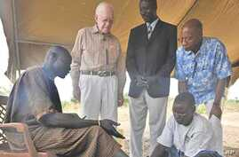 Feb. 11, 2010. Terekeka, Southern Sudan. Former U.S. President and Carter Center Founder Jimmy Carter watches while Garbino, a young farmer with a Guinea worm disease, receives free treatment from a village volunteer trained by The Carter Center in p