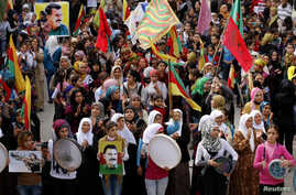 FILE - Protesters carry pictures of Abdullah Ocalan, the jailed leader of the Kurdistan Workers' Party (PKK), during a demonstration in support of Kurdish fighters and the besieged Syrian town of Kobani, in Aleppo, Syria, Nov. 1, 2014.