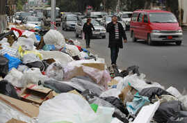 In this Thursday, Dec. 17, 2015 photo, Lebanese citizens pass by a pile of garbage on a street in Beirut, Lebanon. Lebanon's trash collection crisis which set off summer protests is entering its sixth month, but you would hardly be able to know it in