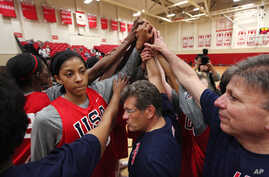 Head coach Geno Auriemma, center, joins Candace Parker, left, and the rest of the US women's basketball Olympic team in a huddle as they complete practice Friday, May 11, 2012, in Seattle.