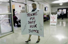 Kelly Jones, ex-wife of Infowars host Alex Jones, carries a sign as she arrives at the Travis County Courthouse, Aug. 1, 2018, in Austin, Texas. Alex Jones wants a Texas judge to dismiss a defamation lawsuit filed against him by families of some of t