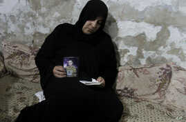 Palestinian Nadia Abu Nada holds a picture of her son Ihab Abu Nada, who set himself on fire because he could not find a job, in Gaza City, September 3, 2012.
