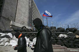 Masked pro-Russian men walk past a barricade outside a regional government building in Donetsk, eastern Ukraine April 21, 2014. An agreement reached last week to avert wider conflict in Ukraine was faltering as the new week began, with pro-Moscow sep