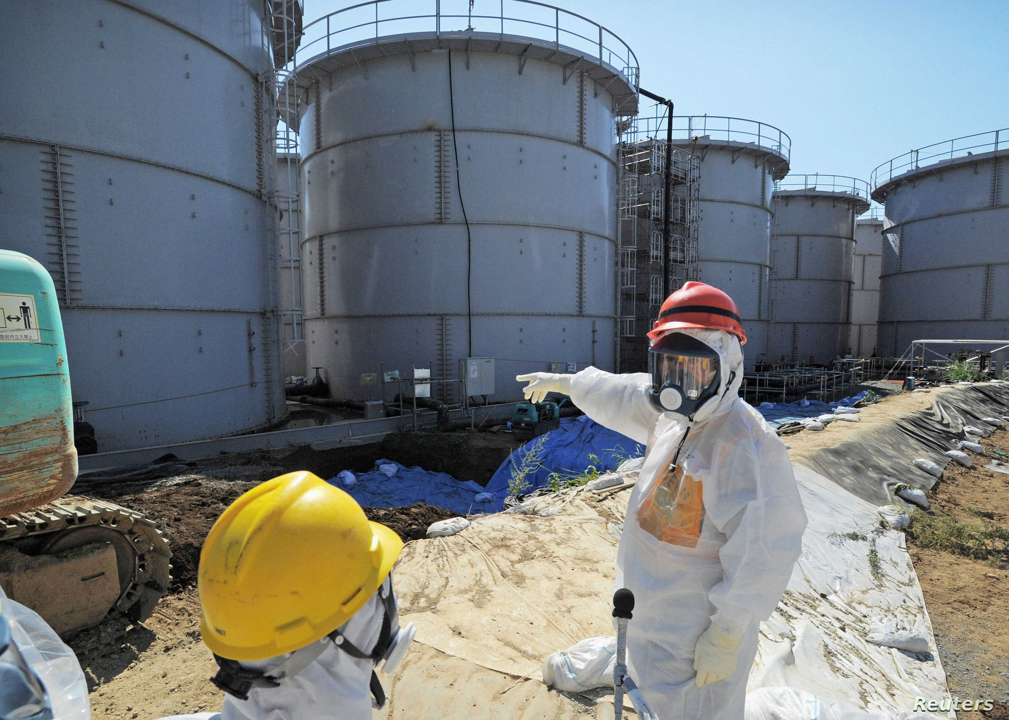 Japan's Economy, Trade and Industry Minister Toshimitsu Motegi (R), wearing a protective suit and a mask, inspects contaminated water tanks at the tsunami-crippled Fukushima Daiichi nuclear power plant in Fukushima prefecture August 26, 2013, in this