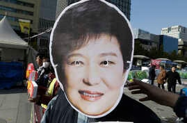 A South Korean protester wears a mask of South Korean President Park Geun-hye during a rally calling for Park to step down in downtown Seoul, South Korea, Nov. 11, 2016. Tens of thousands of South Koreans are expected to march in Seoul to demand Park...