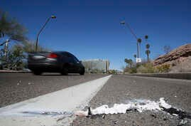 A vehicle goes by the scene of Sunday's fatality where a pedestrian was stuck by an Uber vehicle in autonomous mode, in Tempe, Ariz., March 19, 2018.