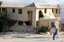 A man walks on crutches past a building destroyed by the earthquake in Leogane, Haiti, Dec. 12, 2010.
