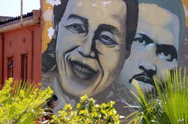FILE - Former South African President Nelson Mandela, left,  is pictured on a mural with South African apartheid freedom fighter Steve Biko, right, in the city of Cape Town, South Africa, March 10, 2013.