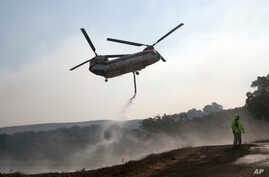 A helicopter draws water from a pond to help put out a fire near Napa, California, Oct. 12, 2017.