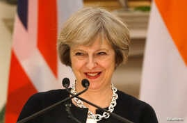 Britain's Prime Minister Theresa May smiles as her Indian counterpart Narendra Modi (unseen) reads a joint statement at Hyderabad House in New Delhi, India, Nov. 7, 2016.